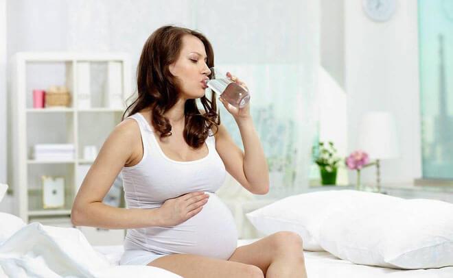 Беременная девушка пьет воду при отравлении